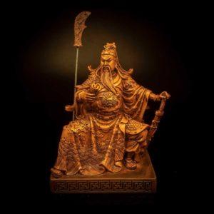 เทพเจ้ากวนอู ไม้ ปางนั่งอ่านตำรามีง้าวตั้ง – GGU001