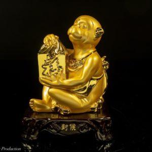 ลิงมงคลถือสมบัติ ฐานไม้  เรซิ่นสีทอง – ZMK002